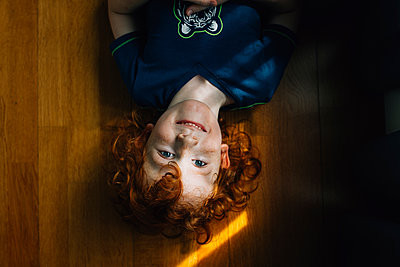 High angle portrait of cute boy lying on hardwood floor at home - p1166m2034911 by Cavan Images