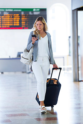 Young businesswoman texting with her mobile phone while walking with suitcase on the hall of the train station - p300m2114529 von Josep Suria