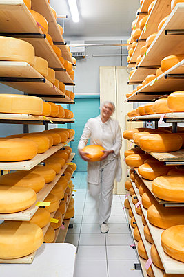Cheese factory, blurred female worker with cheese wheel in storeroom - p300m2199092 by Zeljko Dangubic