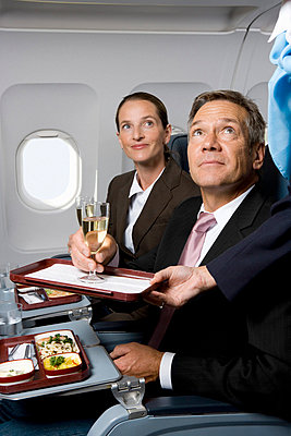 Business people on a plane being served meals and champagne - p3018327f by Halfdark