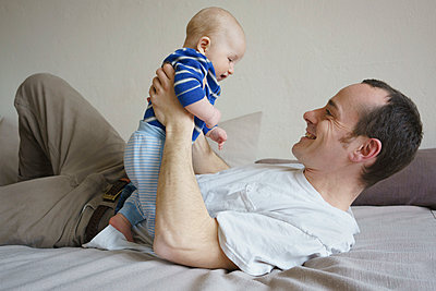 Smiling father holding son and lying on bed at home - p301m1148394 by Halfdark