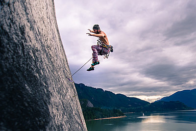 Man with climbing rope jumping off rock face on Malamute, Squamish, Canada - p429m1578408 by Alex Eggermont