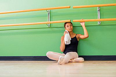 Mixed race ballerina sitting below barre - p555m1463775 by Marc Romanelli