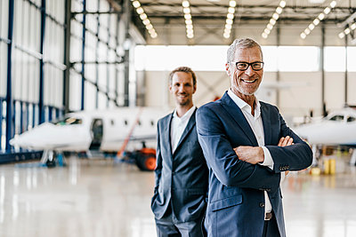 Two businessmen in aircraft hangar - p586m1208562 by Kniel Synnatzschke