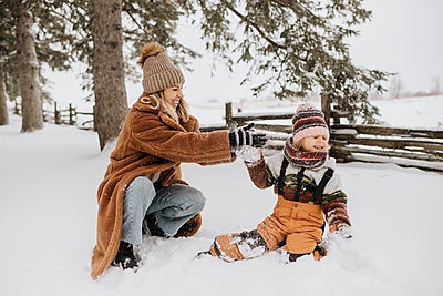 Canada, Ontario, Mother and daughter (2-3) playing in snow - p924m2271197 by Sara Monika