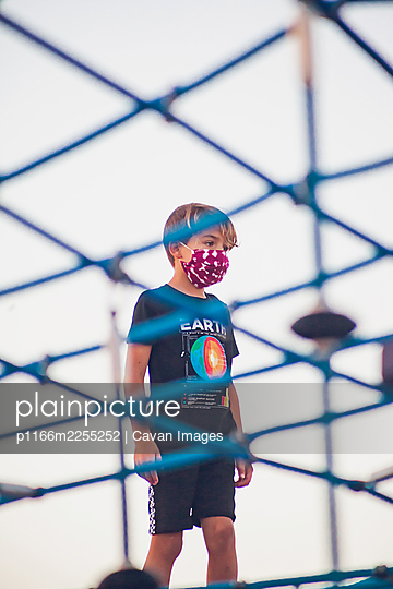 Boy wearing a mask playing alone at a playground - p1166m2255252 by Cavan Images