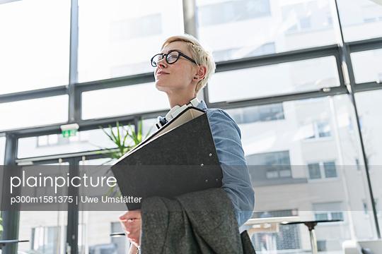 plainpicture - plainpicture p300m1581375 - Smiling woman in office bui... - plainpicture/Westend61/Uwe Umstätter