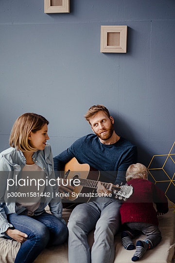 Happy family playing music with their son at home - p300m1581442 von Kniel Synnatzschke