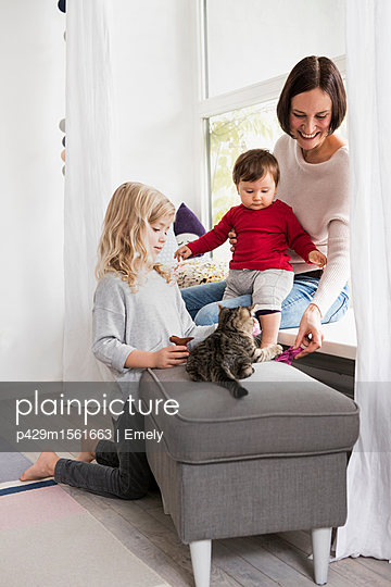 Mother and two daughters playing with pet cat - p429m1561663 by Emely