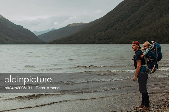 Father with baby on beach, Queenstown, Canterbury, New Zealand - p924m2098131 by Peter Amend