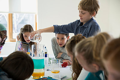 Boys and girls conducting science experiment dining table - p1192m1129572f by Hero Images
