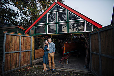 Senior couple standing in front of boathouse - p300m2155250 by Gustafsson