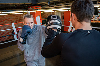 Female boxer sparring with her coach in gym - p300m2171352 by Vasily Pindyurin
