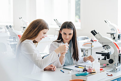 Young female researchers in white coats examining laboratory sample in science class - p300m2250257 by Hernandez and Sorokina