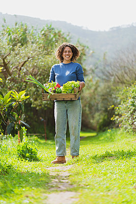 Smiling woman with crate of fresh green vegetables standing in garden - p300m2268096 by Steve Brookland