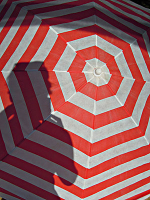 Shadow of person on red striped umbrella - p301m1534994 by Marc Peschke