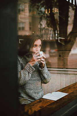 Young woman drinking coffee and reading book at cafe window - p301m2213626 by Toby Mitchell