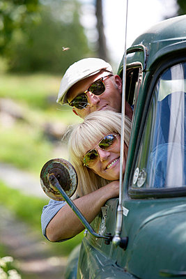 Smiling mature couple looking through cars window - p312m695337 by Hasse Bengtsson