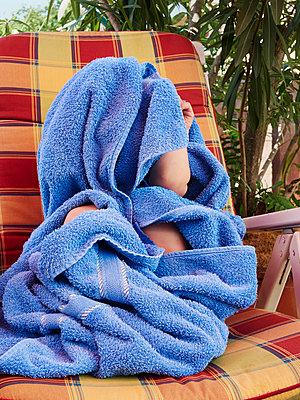 Junge versteckt sich unter einem Badetuch - p358m1160184 von Frank Muckenheim