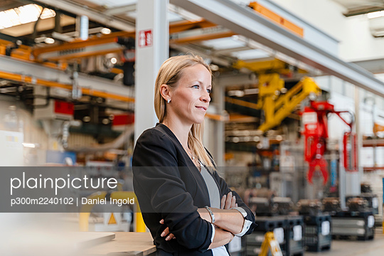 Blond businesswoman with arms crossed looking away while standing in factory - p300m2240102 by Daniel Ingold