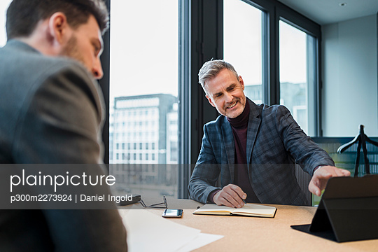 Smiling male professional discussing on digital tablet with colleague at work place - p300m2273924 by Daniel Ingold