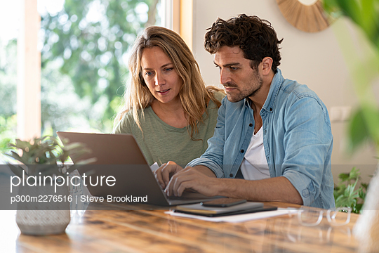 Man using laptop while sitting by girlfriend at table - p300m2276516 by Steve Brookland