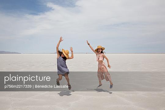 Zwei Mädchen machen Luftsprung in der Wüste - p756m2217339 von Bénédicte Lassalle