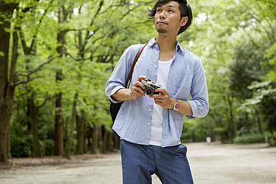 A man in a Kyoto park holding a camera. - p1100m973990f by Liesel Bockl