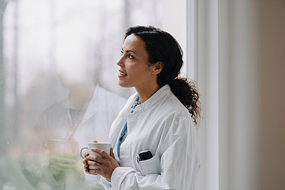 Female doctor looking out of window, holding cup of coffee - p300m2170311 by Joseffson