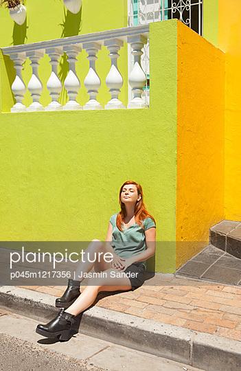 Frau sonnst sich am Straßenrand - p045m1217356 von Jasmin Sander