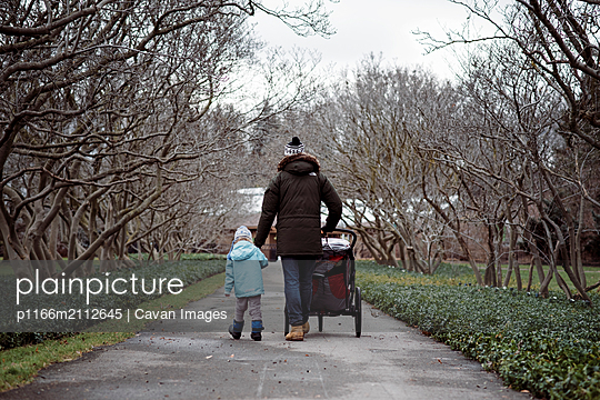 father and daughter holding hands whilst pushing child in stroller - p1166m2112645 by Cavan Images