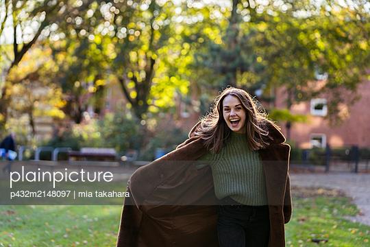 Glückliche junge Frau im Park - p432m2148097 von mia takahara