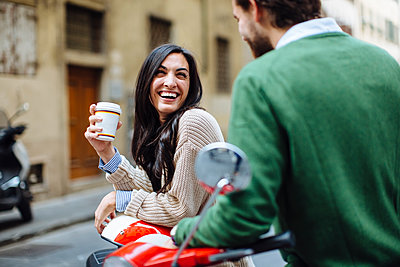Happy woman holding coffee looking at boyfriend while leaning on Vespa - p300m2203023 by Sofie Delauw