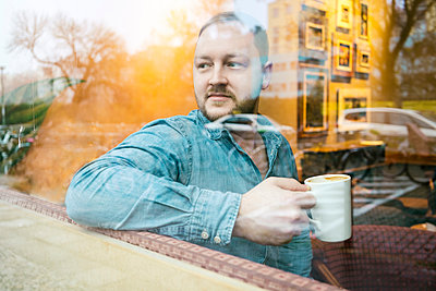 Man in cafe looking out of glass window - p429m2075202 by Tamboly