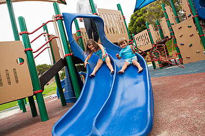 Brother and sister sliding down slide on playground - p555m1479290 by Jihan Abdalla