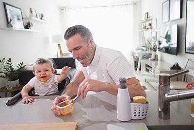 Father feeding happy baby son - p555m1531586 by Jasper Cole
