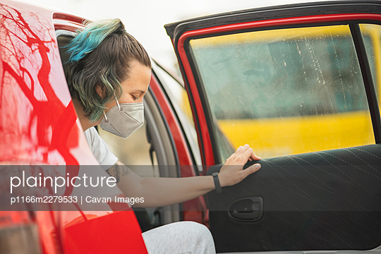 Spanish woman getting out with the mask on from the back of a red car - p1166m2279533 by Cavan Images