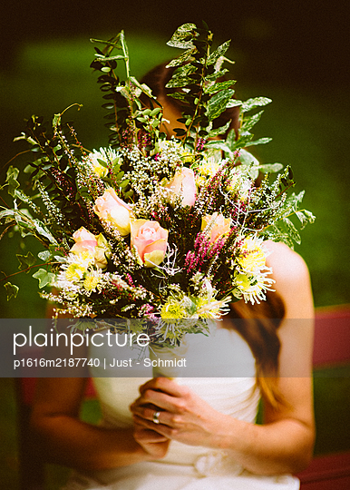 Bride holding big bouquet of flowers - p1616m2187740 by Just - Schmidt