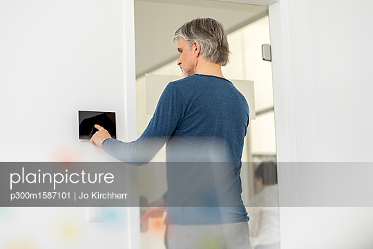 Businessman in office with telecontrol - p300m1587101 von Jo Kirchherr