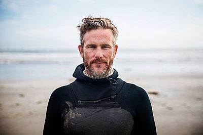 Portrait of confident surfer standing at beach - p1166m1164277 by Cavan Images