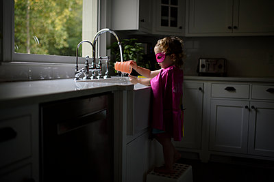 Side view of girl wearing superhero costume washing hands in kitchen sink while standing at home - p1166m2067545 by Cavan Images