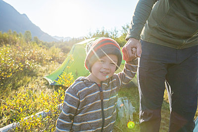 Young boy holding fathers hand while on a camping trip outdoors. - p1166m2212561 by Cavan Images