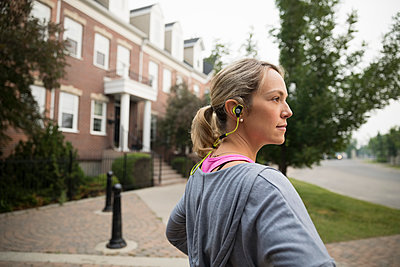 Female runner with earbud headphones looking away on sidewalk - p1192m1490835 by Hero Images