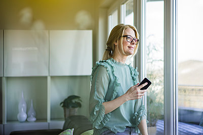 Portrait of content woman with smartphone looking out of window - p300m1588174 by Robijn Page