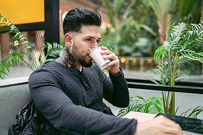 Tattooed hipster man drinking coffee at shop - p300m2252629 by Jose Carlos Ichiro