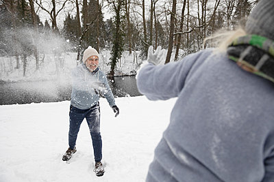 Playful man throwing snow on woman during winter - p300m2281807 by Frank van Delft