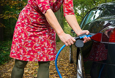Woman charging electric car in forest - p429m1006336f by Mischa Keijser