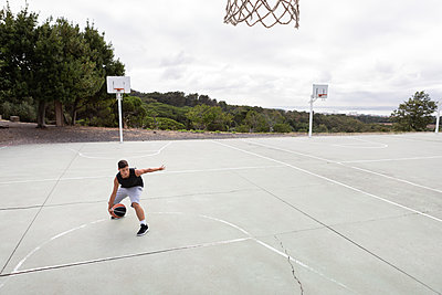 Male teenage basketball player practicing with ball near basketball hoop - p429m2023126 by Gonçalo Barriga