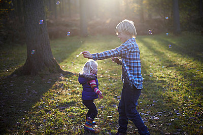 Boy blowing bubbles in forest for toddler girl - p429m803646f by Peter Mason