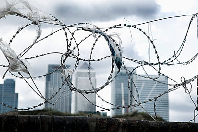 Brick wall with barbed wire on top, plastic bags caught on barbs, Canary Wharf in background; Greenwich Peninsula, London, UK  - p442m839969 by Naki Kouyioumtzis